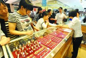 18日,沙重百,大批市民围在黄金柜台前挑选金饰,趁国际金价陡降的时机抄底。 重庆晨报记者 杨新宇 摄