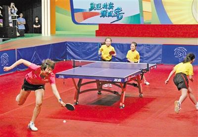 丁宁(左一)与香港小运动员进行乒乓球比赛